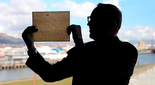 The last letter ever to be written on board the Titanic, which sold at auction recently for a world record sum of £119,000, is inspected by Titanic Belfast CEO Tim Husbands in Belfast. Pic Niall Carson/PA Wire