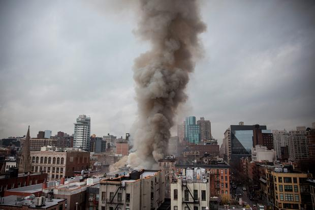 Smoke rises from a burning building after an explosion on 2nd Avenue on March 26, 2015 in New York City (Photo by Andrew Burton/Getty Images)