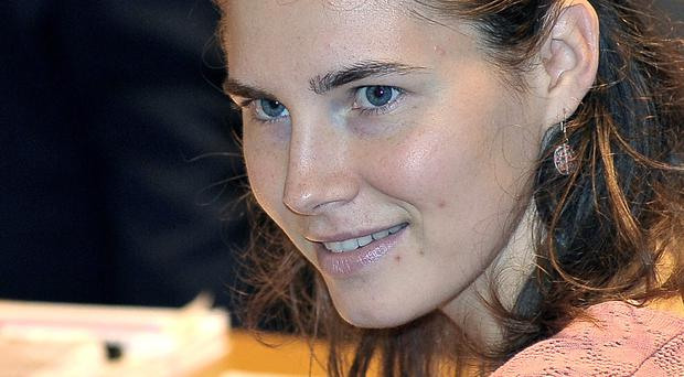 Amanda Knox smiles at the Perugia's court, central Italy. Italy's highest court overturns Friday, March 27, 2015 Amanda Knox murder conviction, closing legal saga. (AP Photo/Stefano Medici, File)