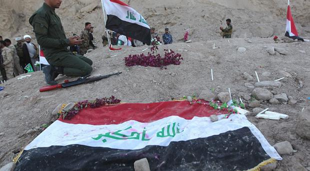 An Iraqi Shiite fighter and member of Iraq's Popular Mobilisation, prays at a burial site believed to hold victims of a June massacre in which hundreds of army cadets were executed by the Islamic State