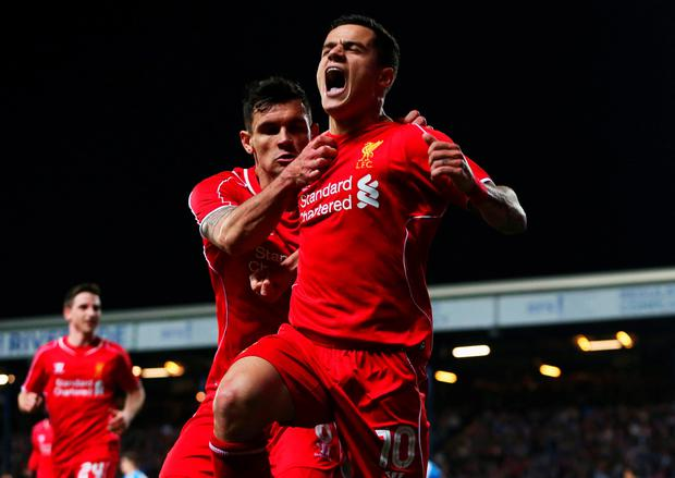 Philippe Coutinho of Liverpool (10) celebrates with Dejan Lovren as he scores during the FA Cup Quarter Final Replay