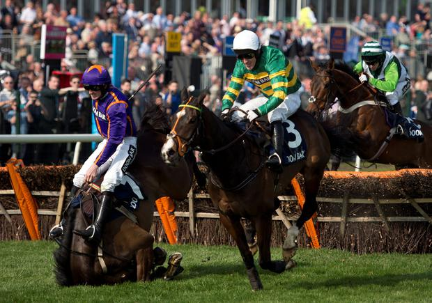 A.P. McCoy riding 'Jezki' (C) crosses the final fence of the 'Doom Bar Aintree Hurdle' first as Ruby Walsh (L) riding 'Arctic Fire' falls, on the opening day of the Grand National Festival horse race meeting at Aintree Racecourse