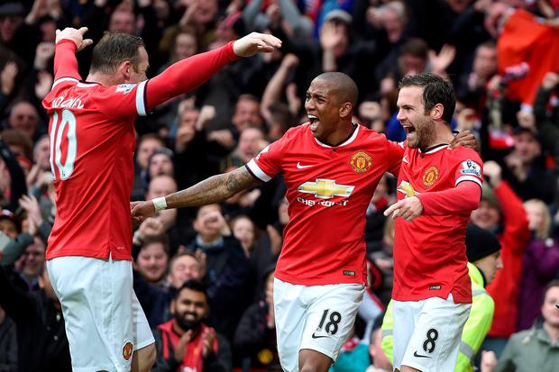 Manchester United's Juan Mata (right) celebrates scoring their third goal of the game with team-mates Ashley Young and Wayne Rooney (left) during the Barclays Premier League match at Old Trafford, Manchester. Martin Rickett/PA Wire.