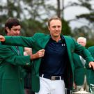 TOPSHOTS Masters defending champion Bubba Watson (L) places the Green Jacket on 2015 Champion Jordan Spieth at the 79th Masters Golf Tournament at Augusta National Golf Club on April 12, 2015, in Augusta, Georgia. AFP PHOTO/DON EMMERTDON EMMERT/AFP/Getty Images