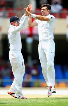 High five: England's James Anderson (right) after taking Devon Smith's wicket