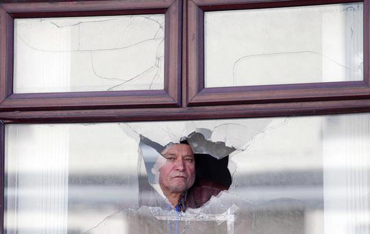 House in Lurgan damaged in overnight shooting. Camille Capraz, who is originally from Turkey inspects the damage to his house on Derry Street in the town. Picture by: Jonathan Porter / Press Eye