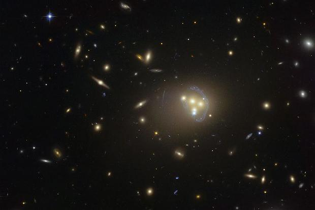 The discovery that dark matter trails behind galaxies in this way suggests it is not perfectly dark after all. Above: Galaxy cluster Abell 3827 seen through the Hubble Space Telescope (ESO)