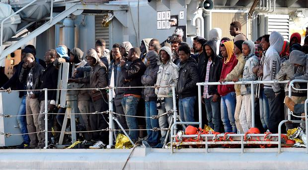 Migrants stand on the deck of the Italian Navy ship