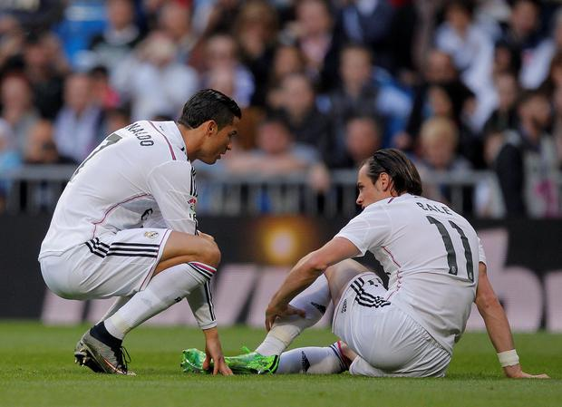 Real Madrid's Gareth Bale, right, gestures after he got injured as Real Madrid's Cristiano Ronaldo, left, looks at him during a Spanish La Liga soccer match between Real Madrid and Malaga at the Santiago Bernabeu stadium in Madrid, Spain, Saturday, April 18, 2015. (AP Photo/Andres Kudacki)