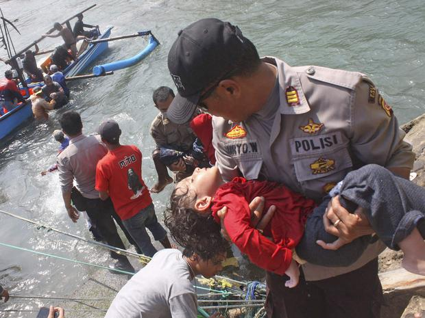 A police officer carries a child survivor who was on the boat full of asylum seekers that capsized off the coast of Sukapura, Indonesia.