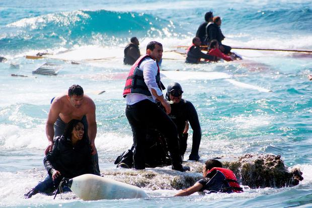 Local residents and rescue workers help a migrant woman after a boat carrying migrants sank off the island of Rhodes, southeastern Greece, on April 20, 2015. At least three people, including a child, died when a boat carrying more than 80 migrants sank off the Greek island of Rhodes.