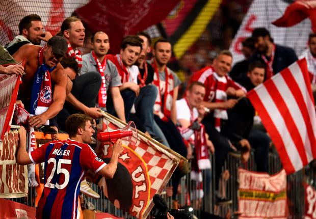 Thomas Mueller of Bayern Muenchen celebrates with fans after victory in the UEFA Champions League Quarter Final (Photo by Dennis Grombkowski/Bongarts/Getty Images)