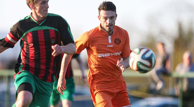 Chasing down: Carrick's Conor McCloskey keeps an eye on PSNI ace Jordan Dane at Newforge
