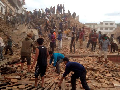 Volunteers help with rescue work at the site of a building that collapsed after an earthquake in Kathmandu, Nepal, Saturday, April 25, 2015.(AP Photo/ Niranjan Shrestha)