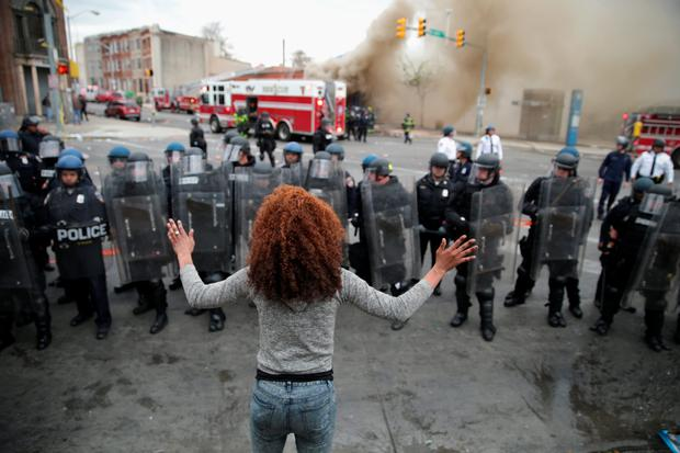 BALTIMORE, MD - APRIL 27: A woman faces down a line of Baltimore Police officers in riot gear during violent protests following the funeral of Freddie Gray April 27, 2015 in Baltimore, Maryland. Gray, 25, who was arrested for possessing a switch blade knife April 12 outside the Gilmor Homes housing project on Baltimore's west side. According to his attorney, Gray died a week later in the hospital from a severe spinal cord injury he received while in police custody. (Photo by Chip Somodevilla/Getty Images)