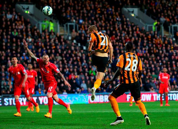 Head boy: Michael Dawson leaps to power home Hull's winner at the KC Stadium