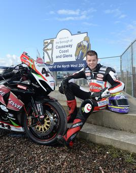 Positive signs: Jamie Hamilton with the Burrows Engineering Cookstown Suzuki at the new Causeway Coast and Glens North West 200 sign at the race paddock