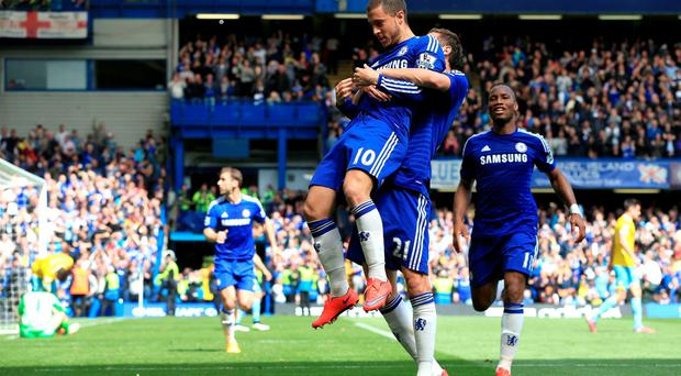 Chelsea's Eden Hazard celebrates with teammates after missing his penalty but scoring with the rebound header during the Barclays Premier League match at Stamford Bridge, London. Nick Potts/PA Wire.