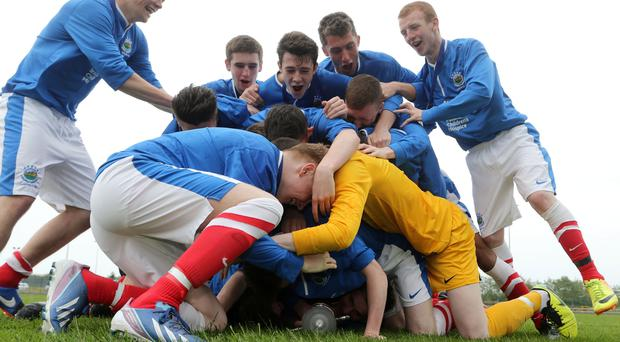 Linfield captain Jordan Malone is buried beneath his celebrating team mates after their Under 17 cup win over Ardoyne YC in the 2014 NIBFA final