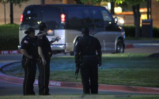 Police officers stands guard at a parking lot near the Curtis Culwell Center where a provocative contest for cartoon depictions of the Prophet Muhammad was held Sunday, May 3, 2015, in Garland, Texas. The contest was put on lockdown Sunday night and attendees were being evacuated after authorities reported a shooting outside the building. (AP Photo/LM Otero)