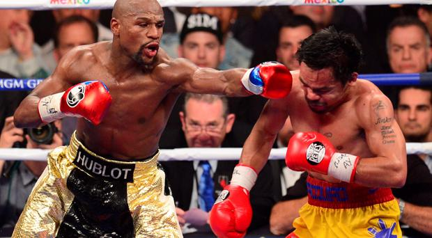 Floyd Mayweather Jr. (L) connects against Manny Pacquiao (R) during their welterweight unification bout on May 2, 2015 at the MGM Grand Garden Arena in Las Vegas