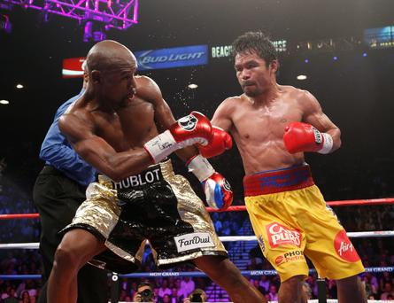US boxer Floyd Mayweather Jr., (L) and Manny Pacquiao of the Philippines fight during their welterweight unification boxing bout at the MGM Grand Garden Arena in Las Vegas, Nevada on May 2, 2015. AFP PHOTO / JOHN GURZINKSIJOHN GURZINSKI/AFP/Getty Images