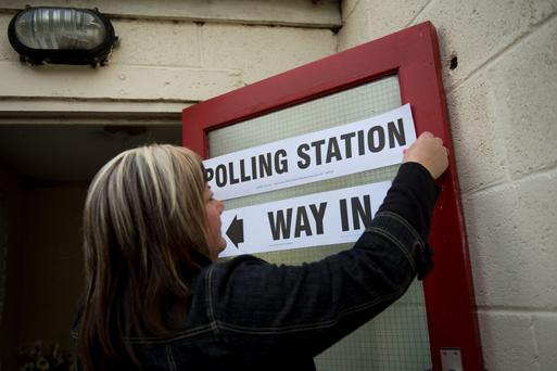 A woman attaches a sign directing voters to the polling station on May 7, 2015