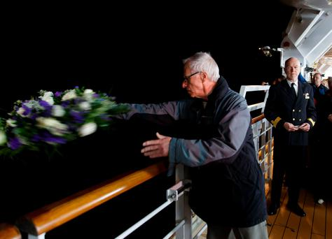 A passenger throwing a wreath off the Queen Victoria, moored off the Old Head of Kinsale near Cobh in Ireland.
