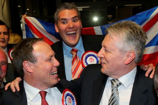 DUP Leader Peter Robinson celebrate their General Election results with MPs Nigel Dodds and Gavin Robinson at the Kings Hall in Belfast.