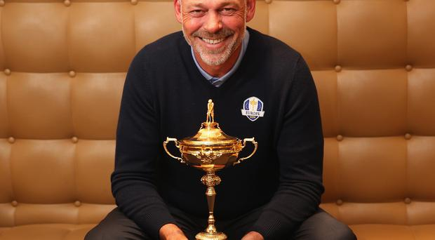 Darren Clarke poses with the Ryder Cup trophy during a Ryder Cup