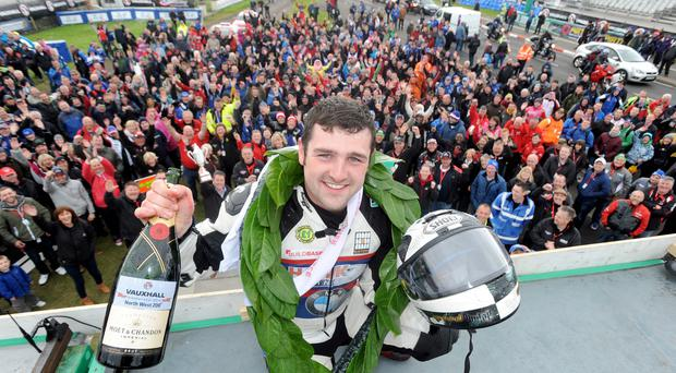 Michael Dunlop celebrates after winning the feature 2014 Superbike race at the Vauxhall International North West 200.