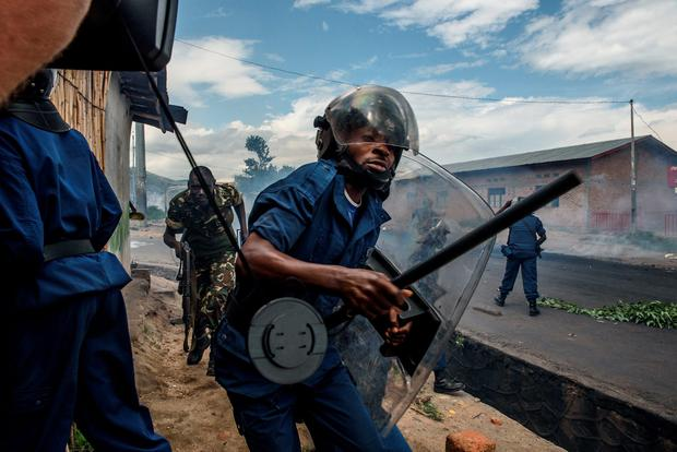 A Burundian police officer holding a baton and army forces run after protestors throwing stones during a demonstration against incumbent president Pierre Nkurunziza's bid for a third term on May 13, 2015 in Bujumbura. AFP/Getty Images