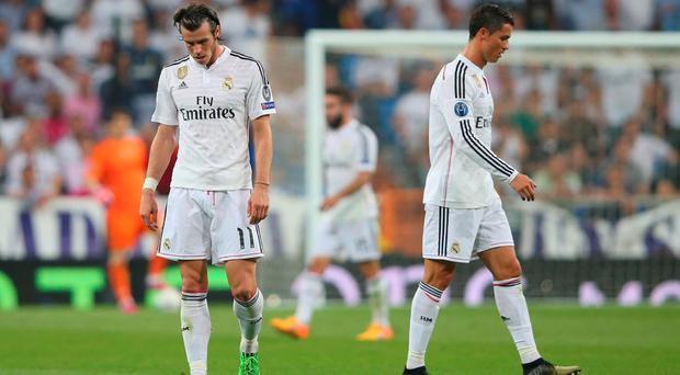 Dejected Real Madrid teammates Gareth Bale and Cristiano Ronaldo walk off the pitch following their team's exit from the competition during the UEFA Champions League Semi Final, second leg match between Real Madrid and Juventus at Estadio Santiago Bernabeu on May 13, 2015 in Madrid, Spain