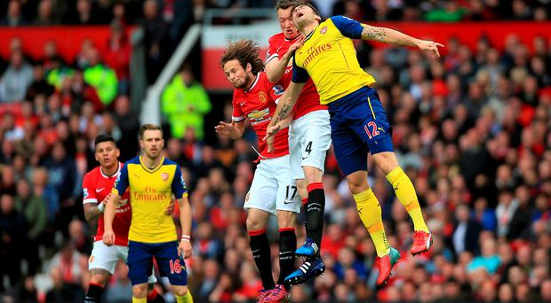 Arsenal's Olivier Giroud (right) jumps with Manchester United's Phil Jones (centre) and Daley Blind during the Barclays Premier League match at Old Trafford, Manchester. Nick Potts/PA Wire.