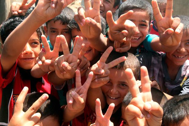 Iraqi children, whose families fled the city of Ramadi after it was seized by Islamic State (IS) group militants, flash the sign of vitory at a camp housing displaced families on May 18, 2015 in Bzeibez, on the southwestern frontier of Baghdad with Anbar province. AFP/Getty Images