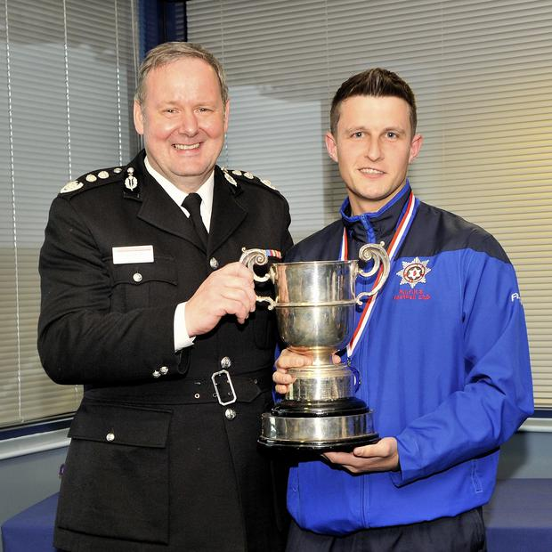 Scottish Fire & Rescue Service Chief Fire Officer Alasdair Hay presenting the UK Fire Service Cup trophy to NIFRS team captain Firefighter Barry Spence.