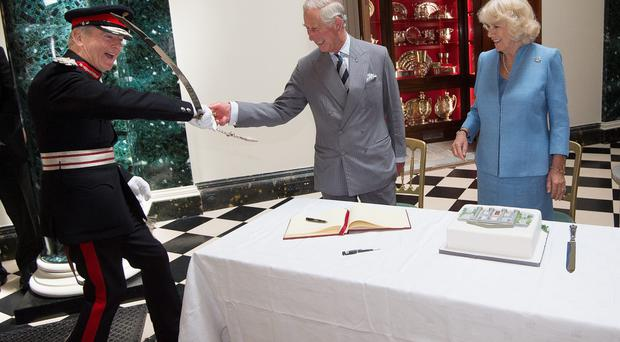 Prince Charles Camilla cut a cake with the help of Mr David Lindsay, HM Lord-Lieutenant of County Down during their visit to Mount Stewart House and Garden on May 22, 2015 in Newtownards, Northern Ireland. (Photo by Eddie Mulholland - Pool/Getty Images)