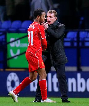 Liverpool's Raheem Sterling shakes hands with manager Brendan Rodgers.