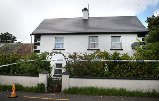 Garda at a farmhouse in Co Limerick where the bodies of Julia Holmes and her partner Tom Ruttle were discovered by suspected burglars. Brian Lawless/PA Wire.