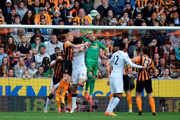 Manchester United's Spanish goalkeeper Victor Valdes (C) comes for a punch from a cross and misses the ball during the Premier League football match between Hull City and Manchester United at the KC Stadium in Kingston upon Hull, May 24, 2015. AFP PHOTO / OLI SCARFF.