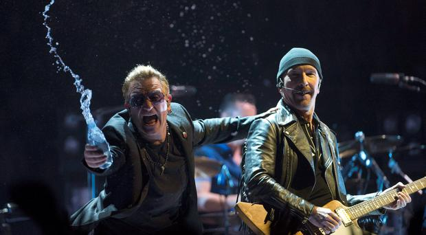 Bono, of the band U2, throws water at the crowd while the Edge watches as they perform in the band's first concert of their new world tour in Vancouver, Thursday, May, 14, 2015. (Jonathan Hayward/The Canadian Press via AP)