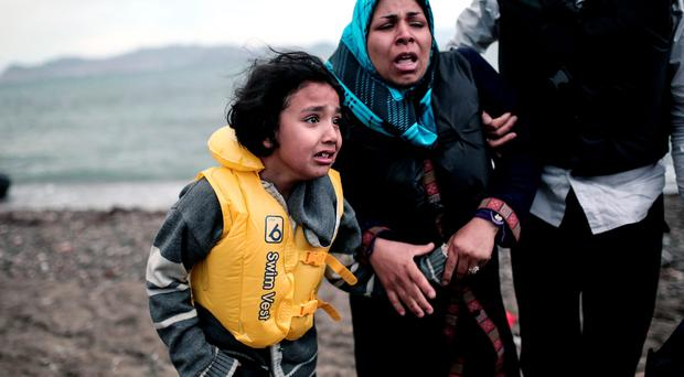 An Afghan migrant girl holds the hand of a woman as they arrive on a beach on the Greek island of Kos, after crossing a part of the Aegean Sea between Turkey and Greece, on May 27, 2015.