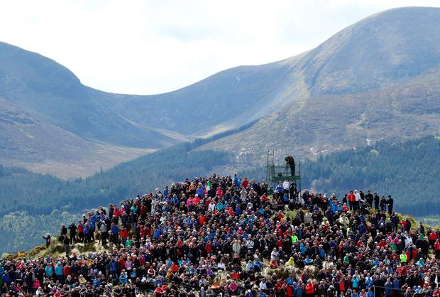 The crowd fills a hill at the 5th hole with the mountains of Mourne in the background on the second day of the Irish Open at the Royal County Down Golf Club in Newcastle in Northern Ireland on May 29, 2015. AFP PHOTO / PAUL FAITHPAUL FAITH/AFP/Getty Images