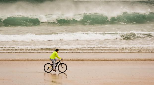 A cyclist rides along the beach at Tolcarne Beach, Newquay, Cornwall, as the great British summer is getting off to a blustery start with severe wind warnings issued nationwide as hopes of a heatwave are thwarted. PRESS ASSOCIATION Photo. Picture date: Monday June 1, 2015. The Met Office has warned that this week will begin with an unseasonably windy spell and even heavy rain despite bookies having slashed the odds on Britain enjoying the hottest June on record. See PA story WEATHER Summer. Photo credit should read: Ben Birchall/PA Wire
