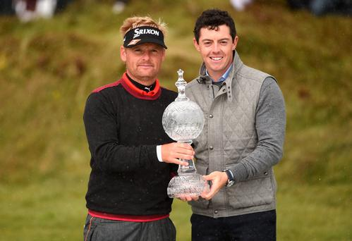 Soren Kjeldsen of Denmark receives the trophy from Rory McIlroy after his victory in a playoff during the final round of the Irish Open