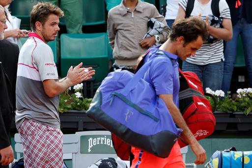 On his way: Stan Wawrinka applauds Swiss compatriot Roger Federer after knocking him out of the French Open
