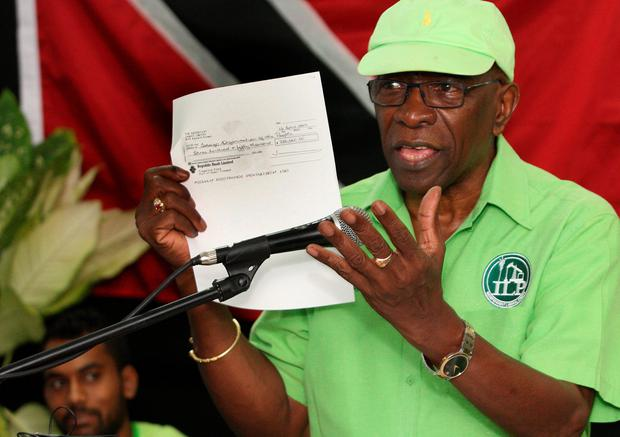Former FIFA vice president Jack Warner hold a copy of a check while he speaks at a political rally in Marabella, Trinidad and Tobago, Wednesday, June 3, 2015.