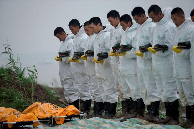 Rescuers paying a silent tribute to recovered victims of the capsized Chinese cruise ship in Jianli, central China's Hubei province. AFP/Getty Images