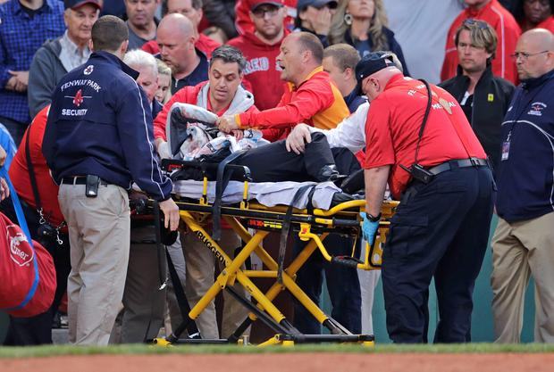 A fan, who was accidentally hit in the head with a broken bat, is helped from the stands during a Boston Red Sox baseball game against the Oakland Athletics at Fenway Park in Boston, Friday, June 5, 2015. (AP Photo/Charles Krupa)