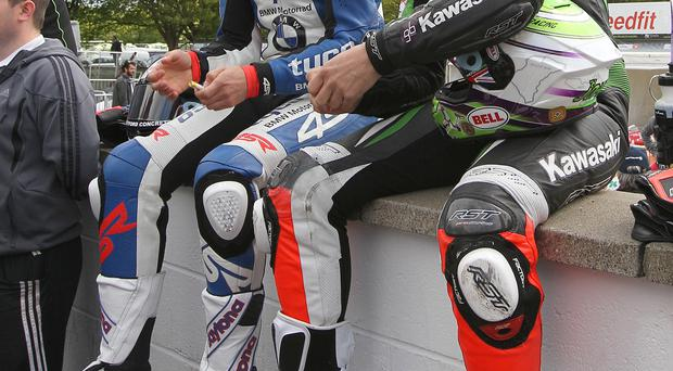 Comparing notes: William Dunlop in discussion with Gary Johnson before breaking his rib in a Superstock crash